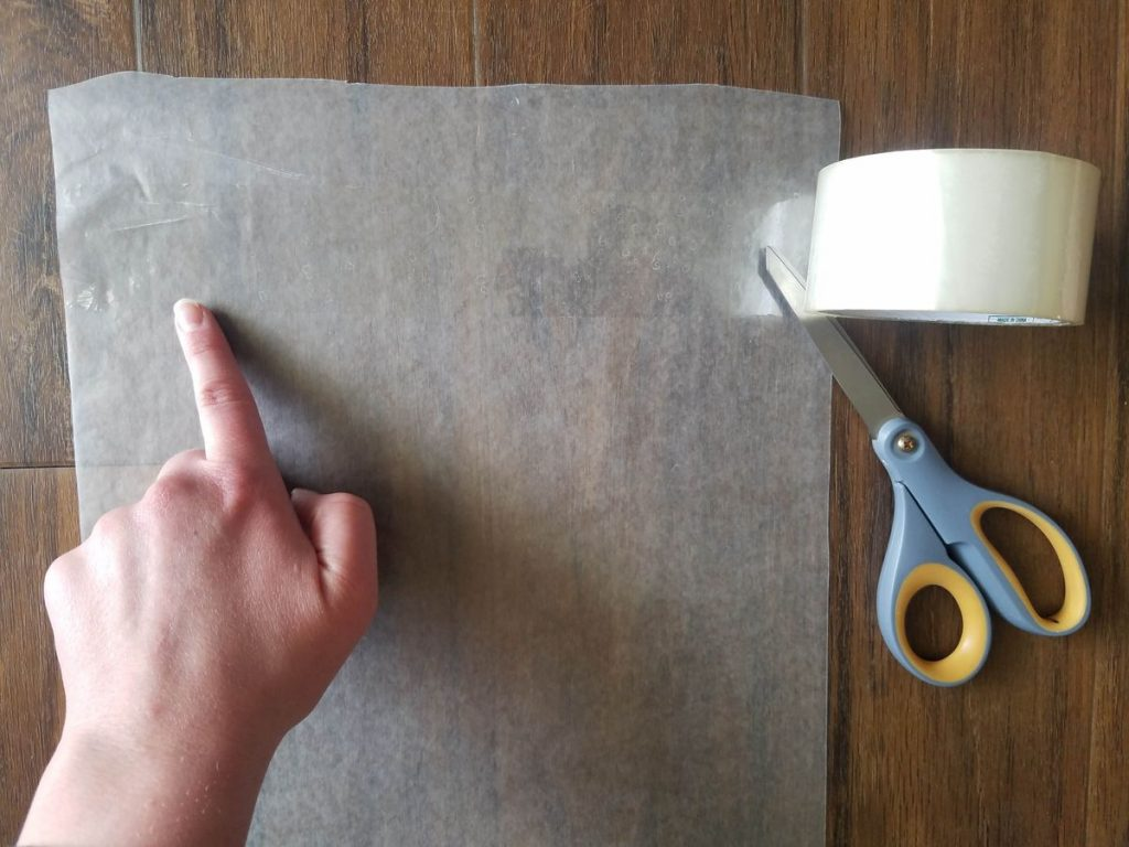 Laying strips of tape onto wax paper